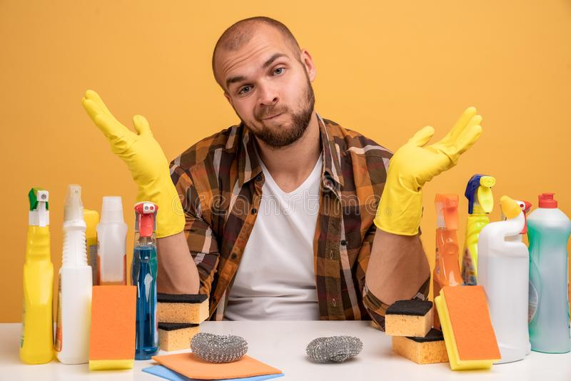 Photo of hesitant uncertain man with clueless expression, shrugs shoulders, doesnt know which detergent to choose for cleaning royalty free stock image