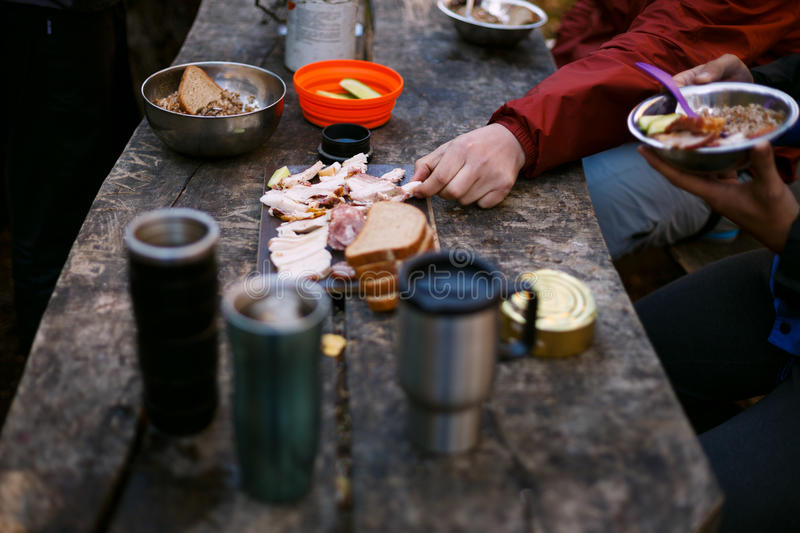 Photo of hiker`s breakfast wooden table with bread, bacon , cans, other meals and hot mugs at the forest camp. People. Camping at national park and doing picnic royalty free stock photography