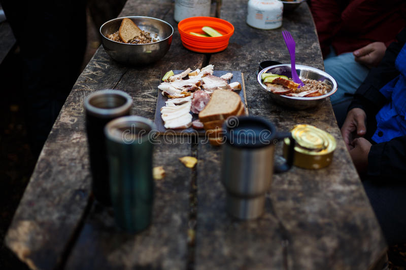 Photo of hiker`s breakfast wooden table with bread, bacon , cans, other meals and hot mugs at the forest camp. People. Camping at national park and doing picnic stock photography