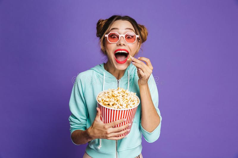 Photo of hipster girl 20s in sunglasses screaming and holding bu. Cket with popcorn isolated over violet background in studio stock photo