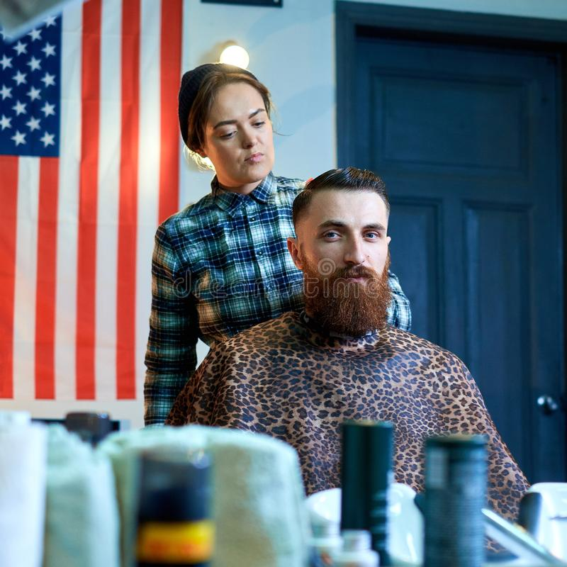 Photo of hipster man getting haircut by hairdresser royalty free stock photo