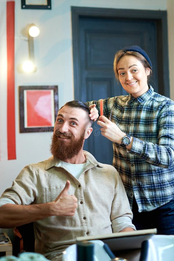 Photo of hipster man getting haircut by hairdresser royalty free stock photos