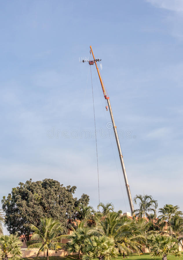 The photo of hoisting crane working for telecommunication site a. Nd antenna tower stock image