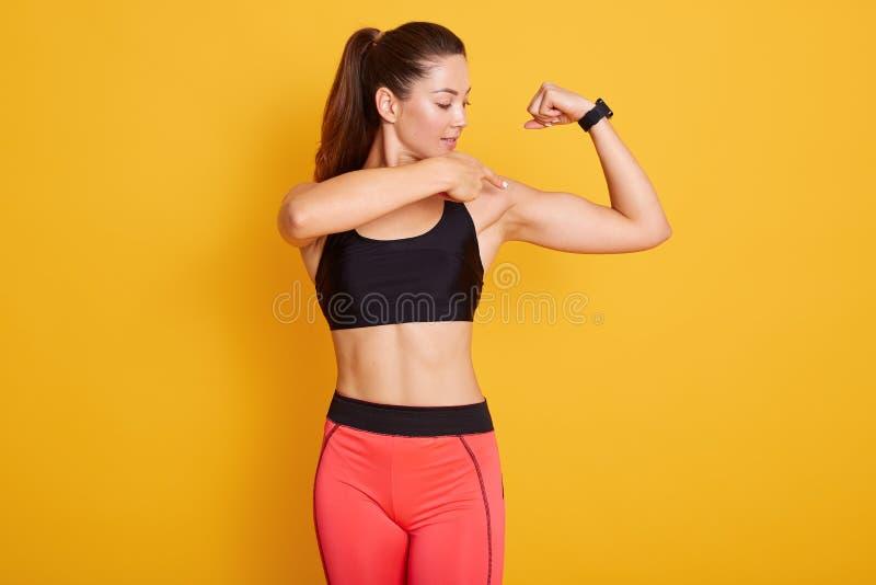 Photo horizontale de la belle jeune femme brune vêtue d'un haut et de leggins noirs, pointant son bicep Longueur de trois quarts photographie stock