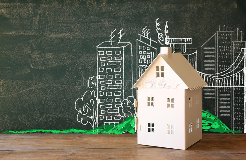 Photo of house and background of blackboard and city drawings. real estate and family house concept royalty free illustration