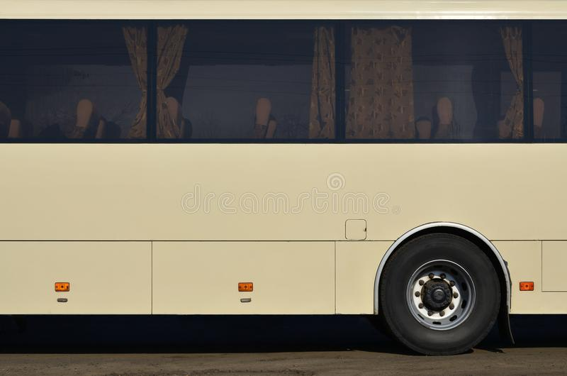 Photo of the hull of a large and long yellow bus with free space for advertising. Close-up side view of a passenger vehicle for t. Ransportation and tourism stock image