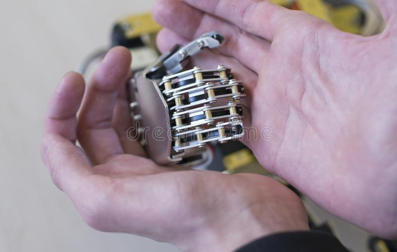 Human hand holding a robot hand. Photo of a human hand holding a robot hand stock photography