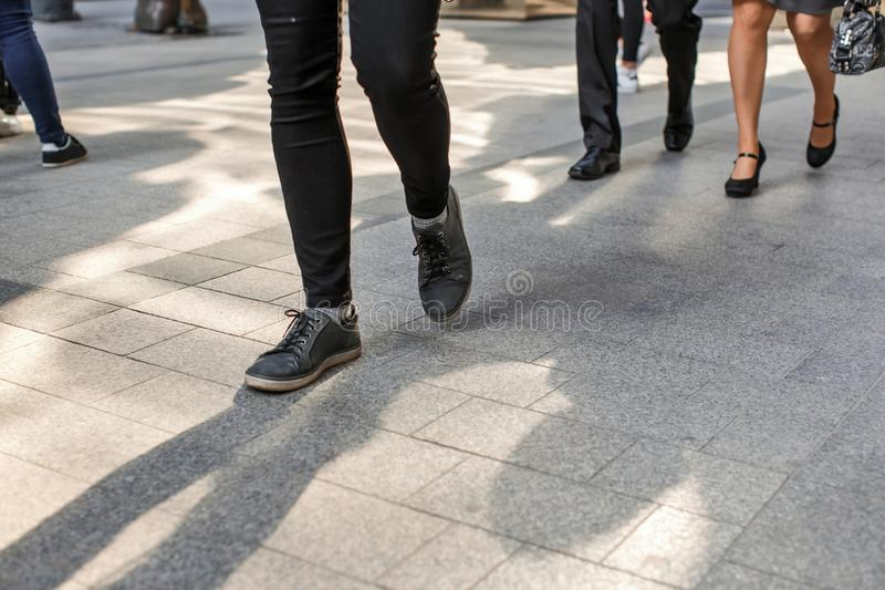 Photo of human legs in different shoes walking on the sidewalk on the street stock photo