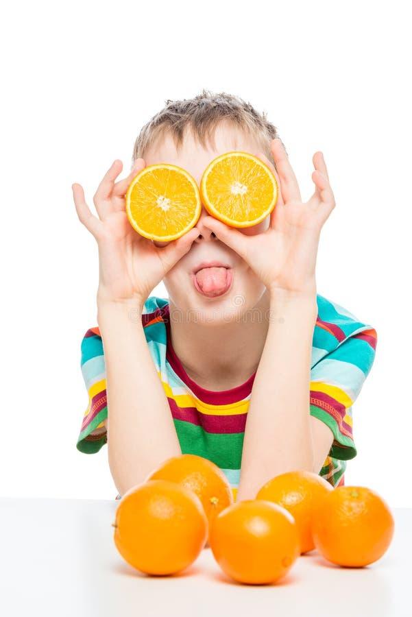 photo humoristique d'un garçon avec des moitiés d'oranges sur un fond blanc photo stock