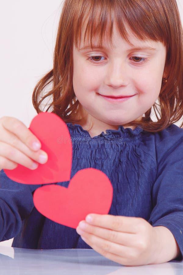 Photo humoristique de la fille mignonne de petit enfant jouant avec les coeurs rouges comme symbole d'amorousness images stock