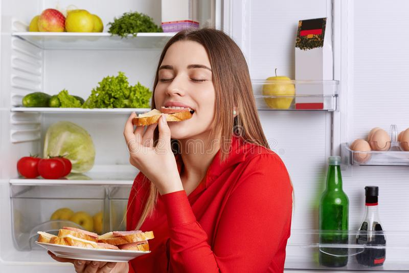 Photo of hungry young cute woman eats with appetite tasty sausage sandwhich, comes after work, stands near opened refrigerator, cl royalty free stock images