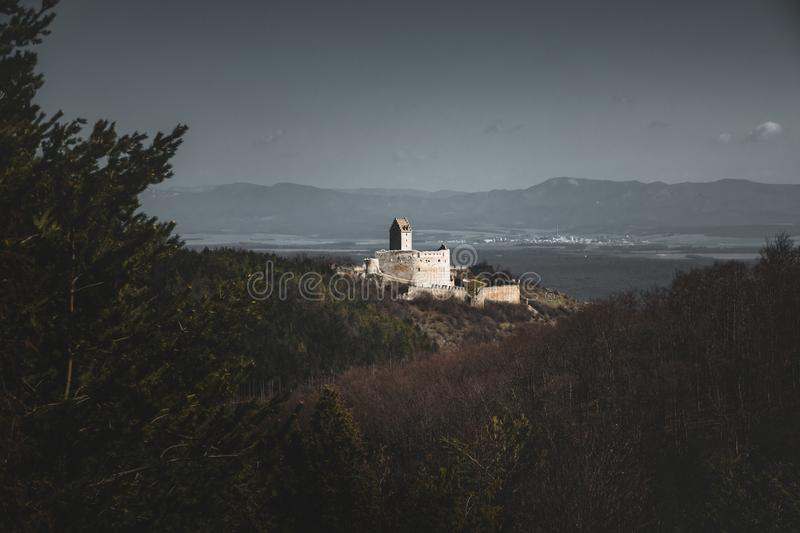 Photo of Illuminated castle with wall on right side in Slovakia - Europe Podhradie. Image of ruins with village on background. Photo from far royalty free stock images