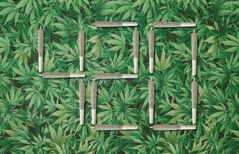 420 Photo illustration on marijuana leaf background. 420 Photo illustration with cannabis joints on marijuana leaf background royalty free stock image