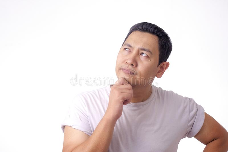 Young Man Thinking and Looking Up, Having Good Idea. Photo image of young Asian man looked happy thinking and looking up, having good idea. Half body portrait stock images