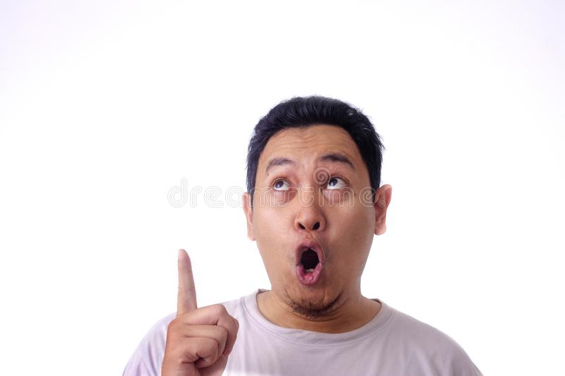 Young Man Thinking and Looking Up, Having Good Idea, with Mouth Open. Photo image of young Asian man looked happy thinking and looking up with mouth opened stock photography