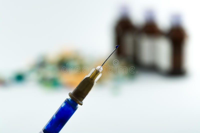 Photo of injection. Syringe with liquid drop on its needle,nozzle over blurry laboratory background royalty free stock photos