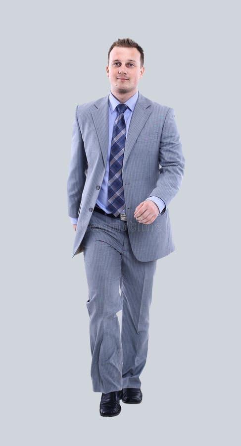Photo intégrale d'un homme d'affaires marchant sur le fond gris photo stock