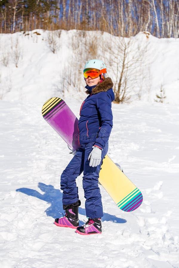 Photo intégrale de casque de port de femme sportive avec le surf des neiges photos libres de droits