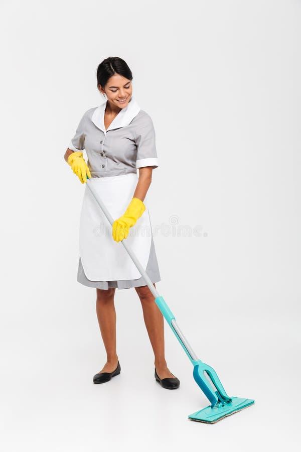 Photo intégrale de femme de charge heureuse dans le plancher uniforme de nettoyage photos libres de droits