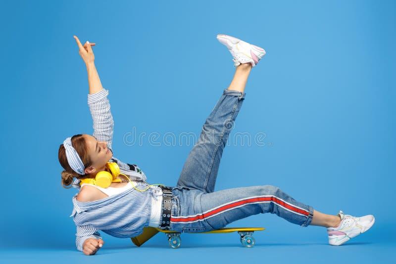 Photo intégrale de jeune femme insouciante heureuse avec les écouteurs jaunes se reposant sur le penny ou la planche à roulettes  photo libre de droits