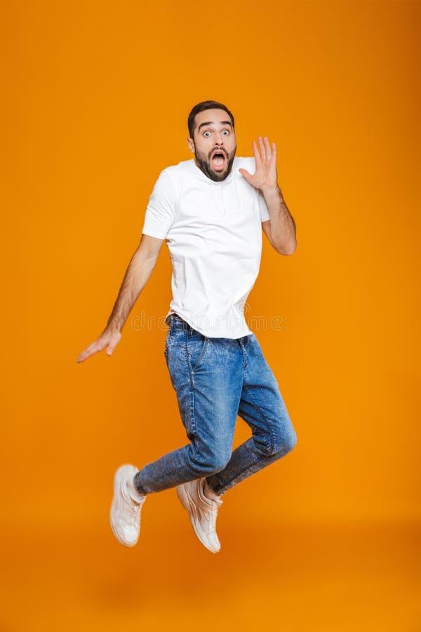 Photo intégrale de type effrayé dans le T-shirt et des jeans sautant et ayant l'amusement, au-dessus du fond jaune photographie stock