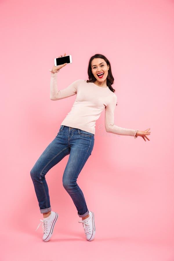 Photo intégrale des jeans de port de la jeune femme 20s démontrant photographie stock
