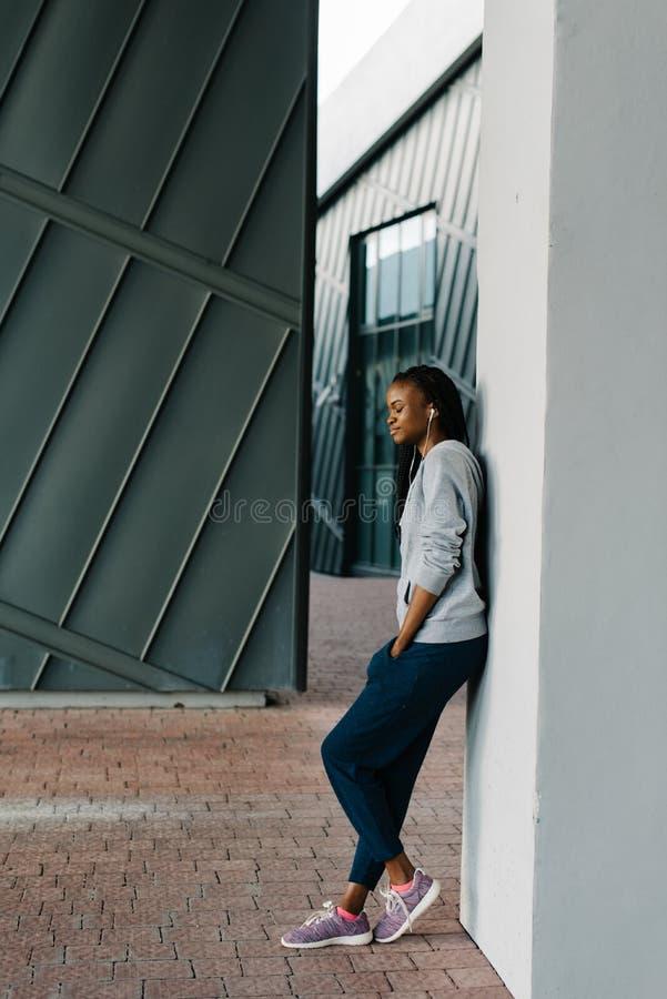 Photo intégrale latérale de l'adolescent avec du charme de forme physique dans les écouteurs se penchant sur le mur La fille est  photographie stock libre de droits