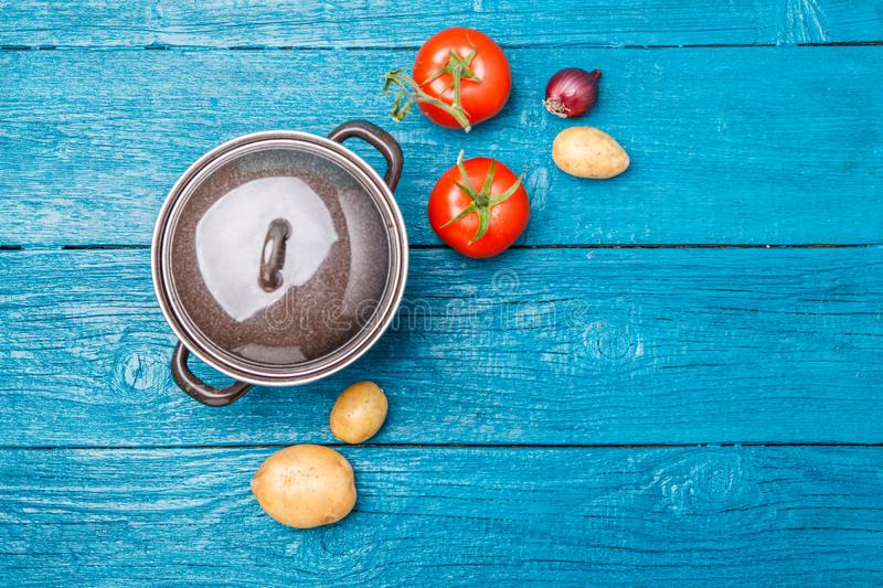 Photo of iron pot, tomato, potato, onion on blue wooden background. stock photos