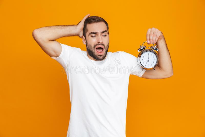 Photo of irritated man 30s in casual wear holding alarm clock, isolated over yellow background royalty free stock images
