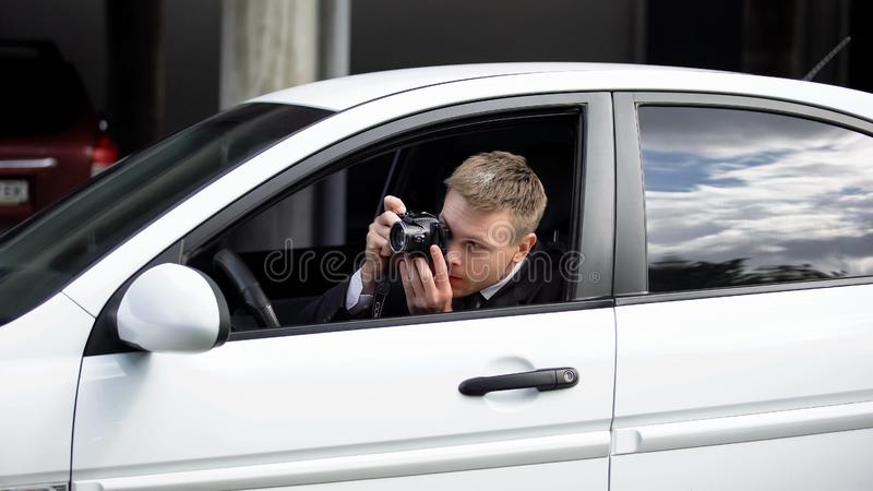 Photo journalist hiding in car taking photos, media employee working outdoors royalty free stock image