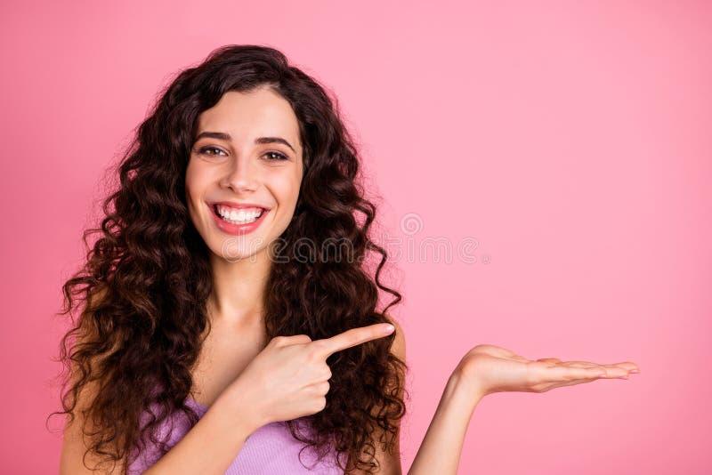 Photo joyeuse, charmante et charmante petite amie pointant son objet sur sa paume, isolée avec un arrière-plan rose photographie stock libre de droits