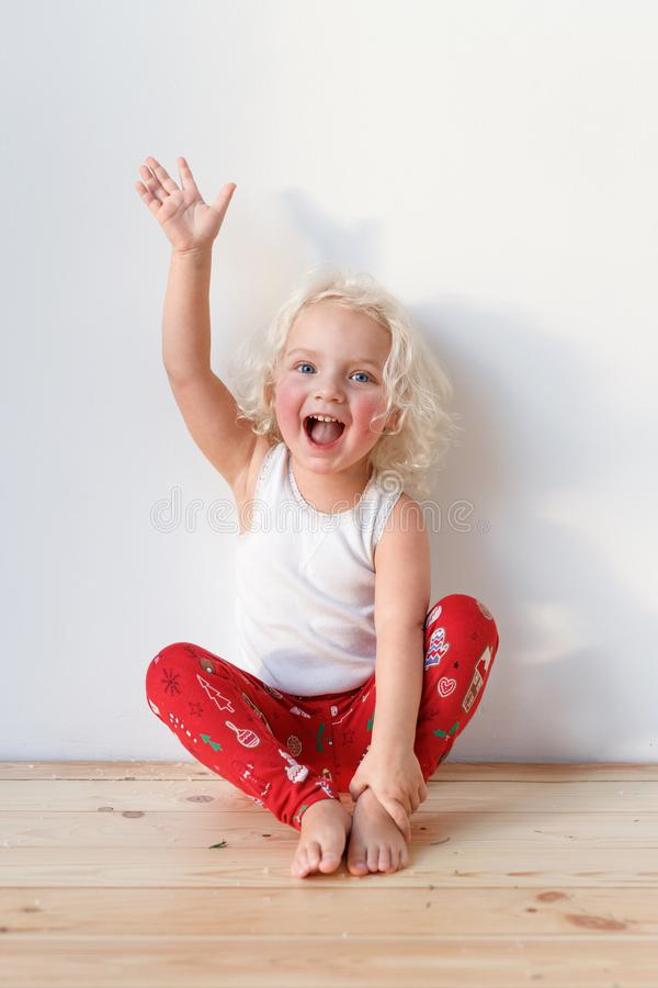 Photo of joyful blonde small kid sits on wooden floor, dressed casually, raises hand, isolated over white background stock photography