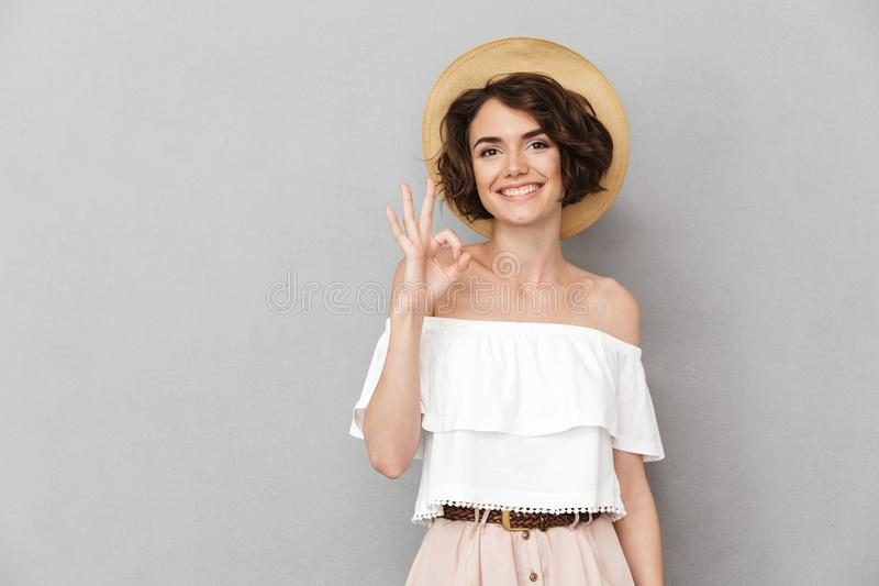 Photo of joyful brunette woman 20s wearing straw hat and summer. Clothing looking at you and gesturing ok sign with fingers isolated over gray background stock photos