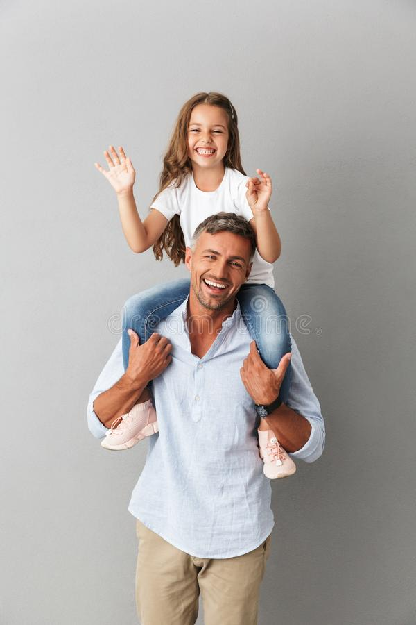 Photo of joyful family smiling at camera while little girl having fun and sitting on the neck of her happy father, isolated over. Photo of joyful family smiling stock image