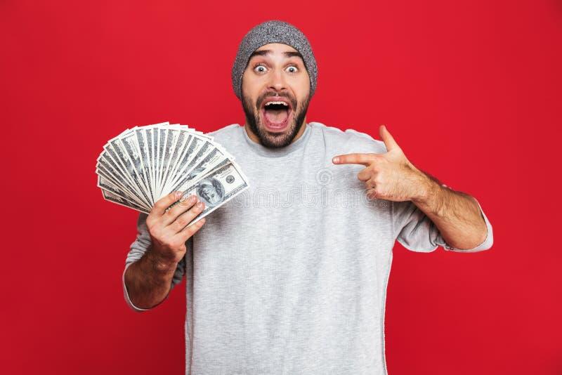 Photo of joyful guy rejoicing and holding cash money isolated over red background. Photo of joyful guy 30s in casual wear rejoicing and holding cash money stock image