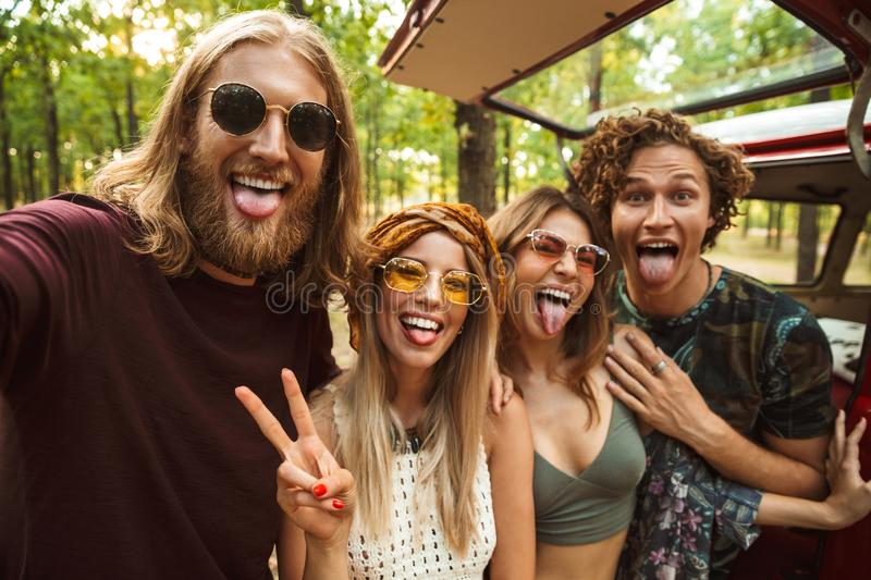 Photo of joyful hippie people men and women, taking selfie in forest near retro minivan stock photos