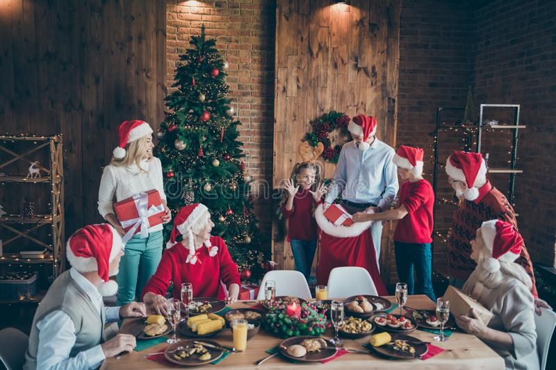 Photo of joyful mature small little people family merry x-mas gathering man in santa claus hat open sack bag give gift. Photo of joyful mature small little stock photography