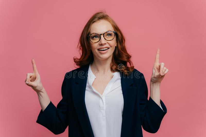Photo of joyful redhaired woman looks above, points fore fingers upwards, has satisfied facial expression, demonstrates something stock photos