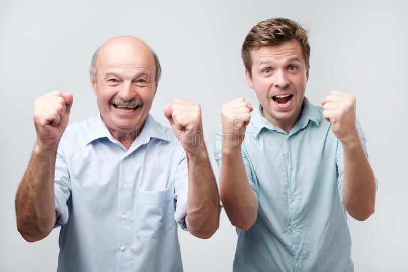 joyful two young men clench fists and shout with happiness, dressed casually, isolated on white background. Happy son and stock photography