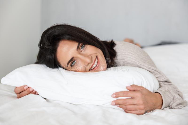 Photo of joyful woman 30s smiling, while lying in bed with white linen at home stock images