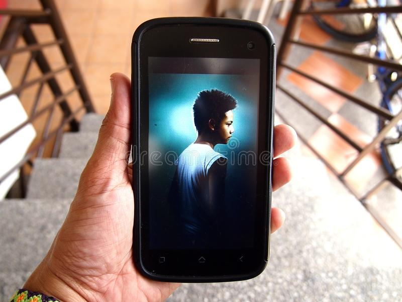 Photo of a kid displayed on a smartphone royalty free stock images