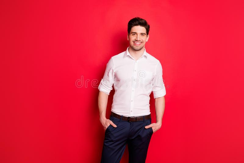 Photo of kind friendly boss standing in front of camera with hands in pockets confidently while isolated with red. Photo of kind friendly boss, standing in front royalty free stock photo