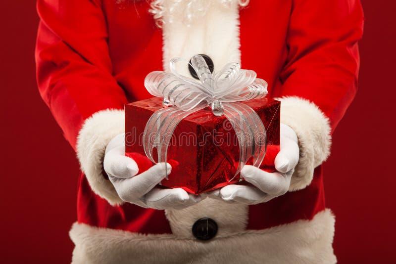 Photo of kind Santa Claus giving xmas present and. Looking at camera royalty free stock photos