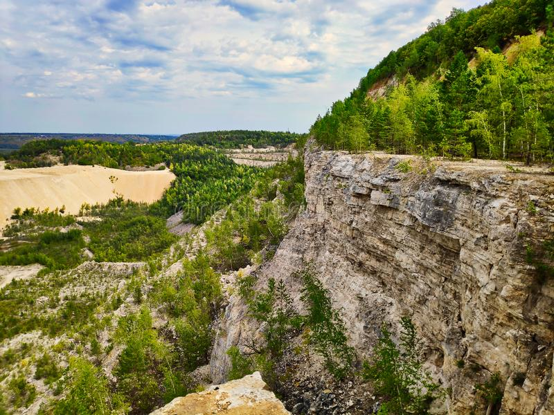 Photo landscape limestone quarry with trees that grow on the slope and below, a mountain of sand and a steep cliff with a cloudy royalty free stock image