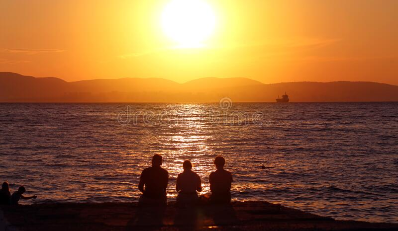 Photo landscape sunset on the sea with a group of people royalty free stock image