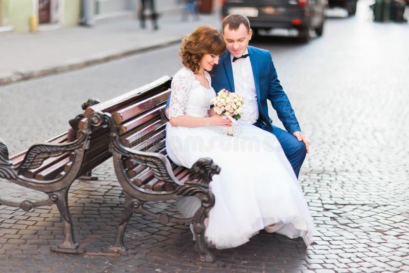 Photo latérale des nouveaux mariés gais s'asseyant sur le banc et tenant le bouquet de mariage image libre de droits