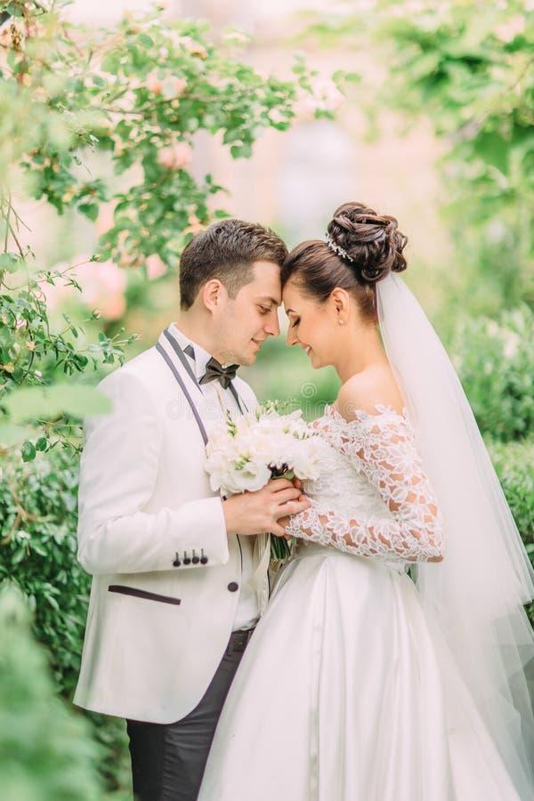 Photo latérale en buste des nouveaux mariés tenant le bouquet de mariage tout en se tenant tête à tête photo libre de droits