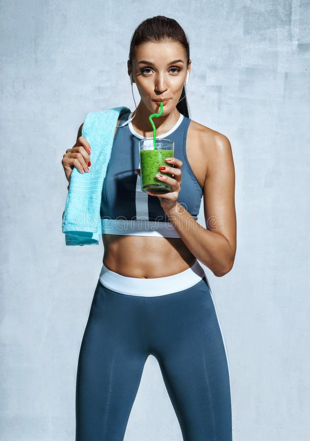 Photo of latin fitness girl with towel and glass of detox cocktail royalty free stock image