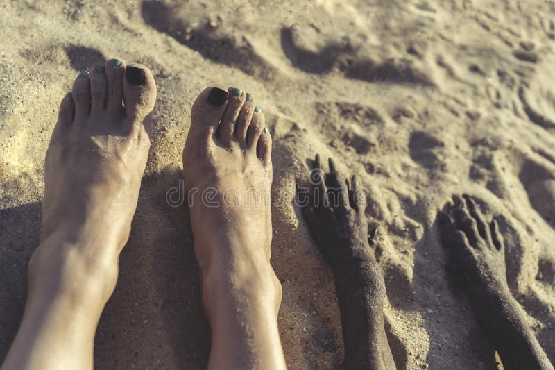 Photo of legs of young girl and paw of dog in sand on summer beach on the walk. selfie feet stock image