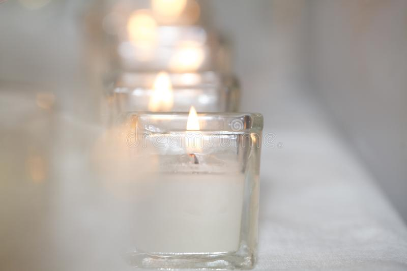 A Line of Candles Give Light. This is a photo about light. A row of candles gives a white light that brightens the whole frame royalty free stock photos